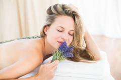 Beautiful blonde lying on massage table with lavanda Stock Photos