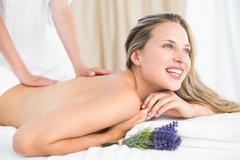 Beautiful blonde lying on massage table with lavanda - stock photo