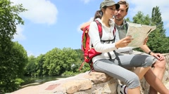 Couple of backpackers reading map, sit on bridge Stock Footage