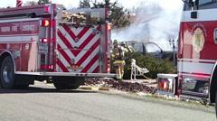 Firemen mop up a vehicle fire Stock Footage