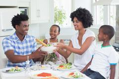 Happy family sitting down to dinner together - stock photo