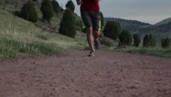 Runner runs past camera on a red dirt trail Stock Footage