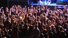 Cheering spectators audience clapping hands up in air on rock concert lumiere Stock Footage
