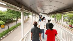View over people crowd in narrow passageway, walk forward, elevated footbridge Stock Footage