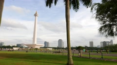 Walk in trees on north park of Merdeka Square, National Monument panning view Stock Footage