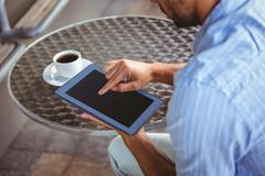 Attentive businessman using a tablet - stock photo
