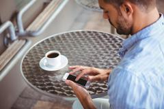 Attentive businessman sending text message - stock photo