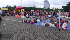 Woman hand bag selling on stone pavement, Merdeka Square, Monas Stock Footage