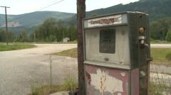 Abandoned gas station pump and highway, logging truck through frame Stock Footage