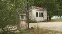 Abandoned overgrown 1960s gas station and garage, static Stock Footage