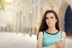 Undecided Woman with Smartphone out in the City Stock Photos