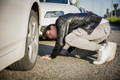 Young Man Examining Underside of Car - stock photo