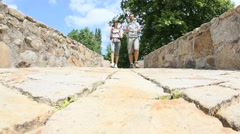 Couple with backpack walking on stone bridge - stock footage