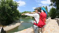 Couple of hikers looking at river from bridge - stock footage