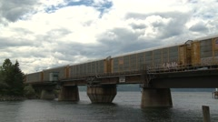 Railroad, auto transporters train over swing bridge Stock Footage