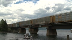 Railroad, auto transporters train over swing bridge end Stock Footage