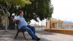 OLD MAN RELAXING ON WATERFRONT PARK  BENCH  - Old San Juan Stock Footage