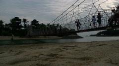 Silhouette of People Walking on Suspension Bridge on Sentosa Island Singapore Stock Footage