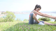 Young fitness woman doing stretching exercises outside Stock Footage