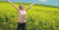 Young caucasian woman in flower field raising opening arms - stock footage