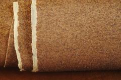 Sandpaper on wooden background - stock photo