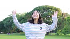 Portrait of thai student teen beautiful girl happy spin around in park Stock Footage
