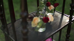 On the antique wooden stand tiny bouquets of roses in glass vases. Stock Footage