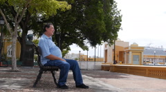 OLD MAN MAKES A CALL ON WATERFRONT PARK  BENCH with cell phone - Old San Juan Stock Footage