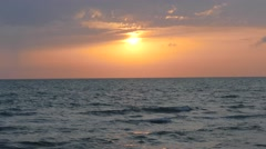 Sun sets into the horizon above the sea Stock Footage