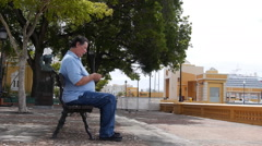 OLD MAN SENDS TEXT MESSAGE ON WATERFRONT PARK  BENCH with cell phone - SAN JUAN  Stock Footage