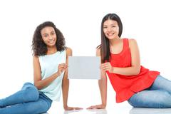 Smiling friends holding sheet of paper Stock Photos