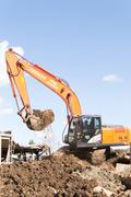 Stock Photo of Orange Hitachi Digger Moving Soil
