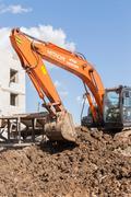 Orange Hitachi Digger Moving Soil - stock photo