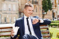 Young man checking time in park - stock photo