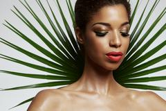 pretty afro woman with a palm leave backside - stock photo