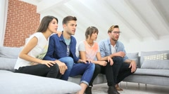 Cheerful group of friends watching football game on tv Stock Footage