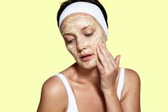 Woman touching her face. facial mask. yellow background Stock Photos