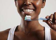 closeup of woman's smile and teethbrush - stock photo