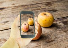 Hand holding smart phone and apple on wooden table background Stock Photos