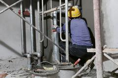 Construction Worker in Tight Corner Under Scaffolding - stock photo