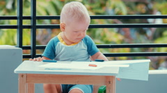 Toddler boy scatters crayons and paper - stock footage