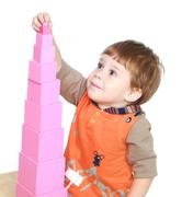 The little boy in Montessori kindergarten collects pink pyramid - stock photo