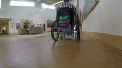 A college student in wheel chair moving down a hallway Stock Footage