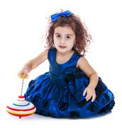 Dark-haired curly-haired little girl spinning dreidel sitting on - stock photo