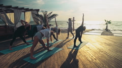Group of women practicing yoga on the beach slow motion Stock Footage