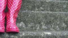 4K Panning in on a staircase where a woman is standing in red wellies with dots Stock Footage