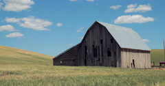 Old abandoned barn in wheat field dolly moving tracking Stock Footage