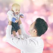 Cheerful baby and dad with bokeh background - stock photo