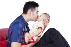 Stock Photo of Dad kiss the lips of baby