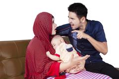 Two parents quarrel while holding a baby - stock photo